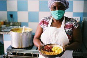 Foto de uma mulher negra, em pé, em frente a um fogão, com um prato com comida nas mãos.
